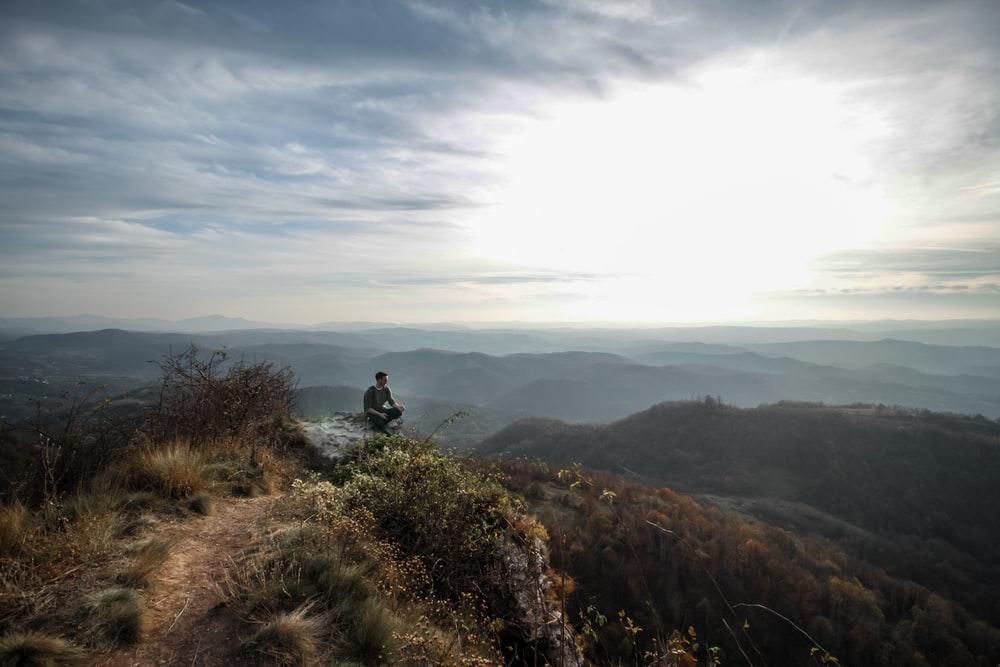 a man sits atop a mountain