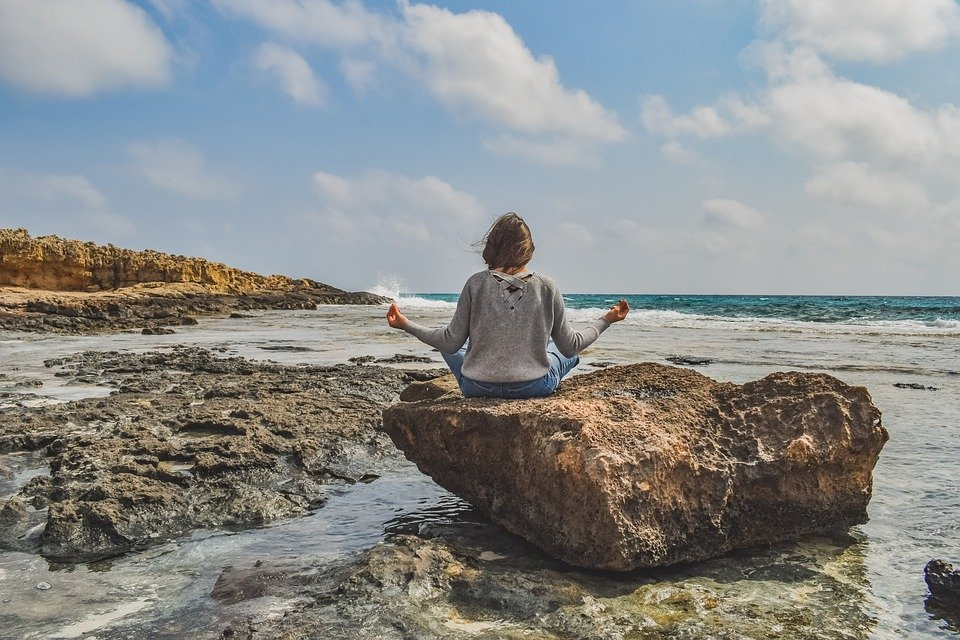 A woman sits on a rock near a beach introspecting and meditating